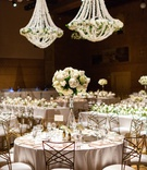 gold chameleon chairs at wedding reception with inverted glass vase with white roses and hydrangeas