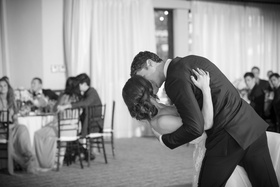 black and white photo of groom dips bride for a kiss during first dance