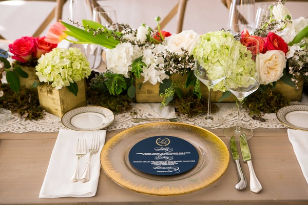 Blue round menu card on gold charger plate on wood table with pink, red, and white flowers