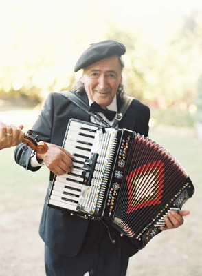 Man in Paris theme beret playing accordion at chic outdoor wedding in Malibu