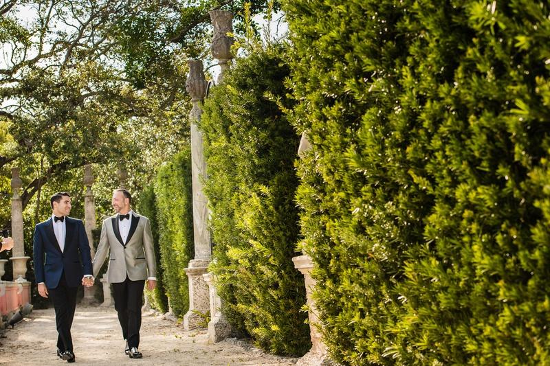 same-sex wedding gay couple, groom in navy tuxedo jacket, groom in grey tuxedo jacket