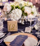 Wedding reception navy linen low centerpiece white hydrangea peony rose table number gold and menu