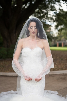 bride in nardos deisgns lace mermaid gown with blusher veil over her head