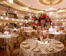 Wedding reception decor ballroom with pink and red flowers gold detailing
