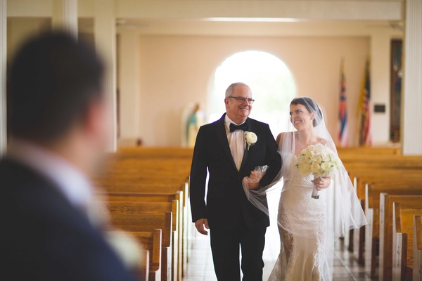 Father of the bride in tuxedo and glasses smiles as he walks daughter down aisle veil over face