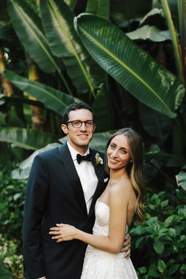 wedding couples groom in glasses and bow tie tuxedo bride in strapless wedding dress long hair down