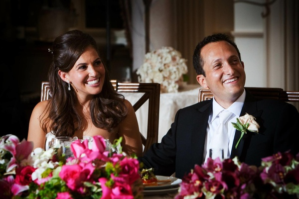 Bride and groom smile at sweetheart table