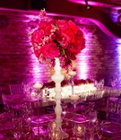 tabletop with pink flowers on white stand, surrounded by tall thin glass candleholders