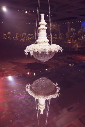seven tiered wedding cake with white flowers suspended on a crystal chandelier