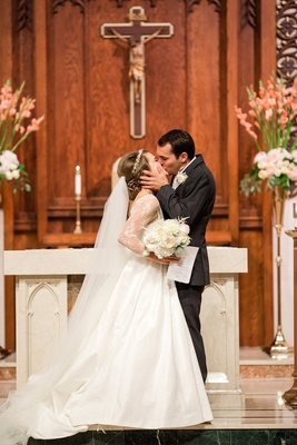 Bride and groom kiss in front of altar at Catholic Church