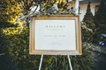 printed wedding welcome sign in gold frame with greenery on top