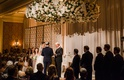 bride and groom with rabbi wedding ceremony hanging flower chuppah chandelier lighting romantic