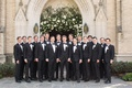 groom with groomsmen in matching suits and bow ties ivory flower boutonniere in front of church arch
