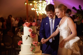 wedding photo of bride and groom cutting into white buttercream wedding cake decorated pink flowers