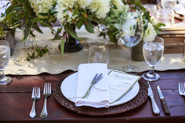 Ranch wedding wood reception table with rattan charger, lavender bundle on white napkin