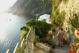 Bride and groom walk down steps of Cinque Terre cliff