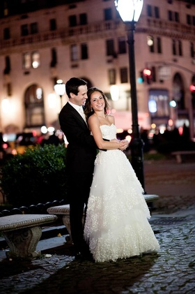Bride and groom embrace in square in NYC