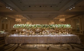 a long table with a white linen featuring tall white-and-green arrangements connected ghost chairs