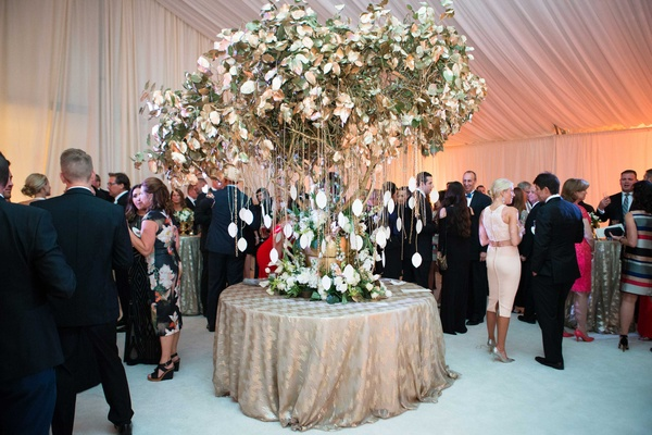 Gold tree wedding reception escort card table display with seating assignments hanging from chains