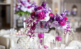 Wedding reception with stock, peonies, hydrangeas, orchids in violet, lilac, & fuchsia tones