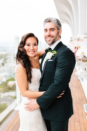 Bride in wedding dress hugging groom in tuxedo boutonniere on balcony of mr c beverly hills