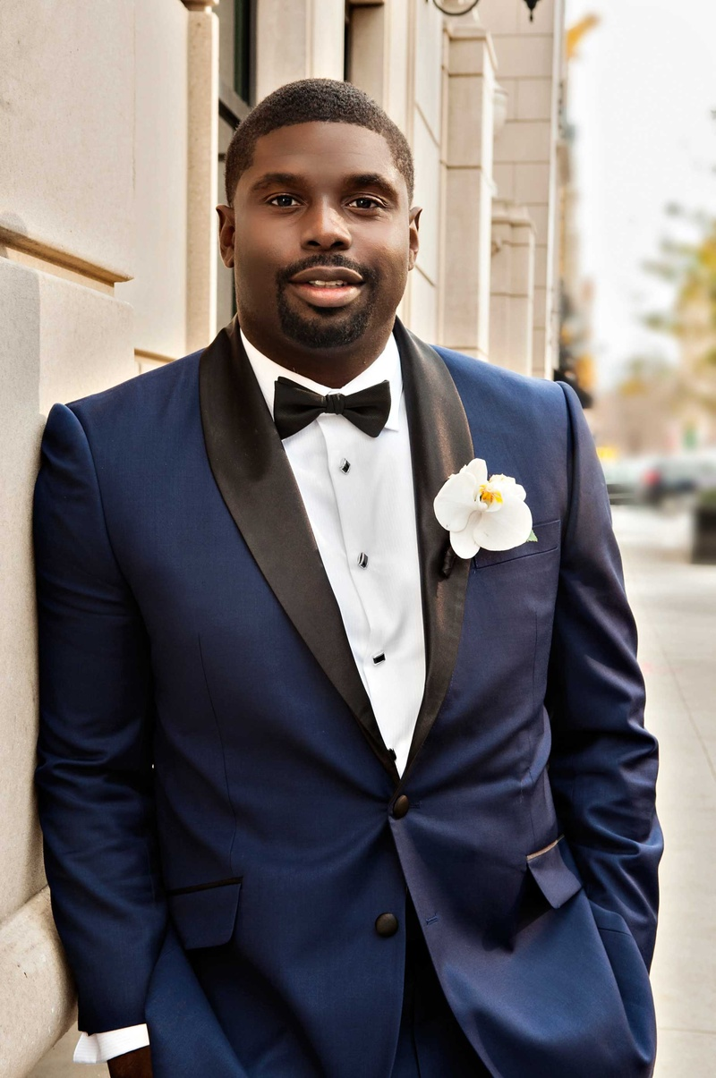 African American groom with custom made navy blue tuxedo with black lapel bow tie orchid boutonniere