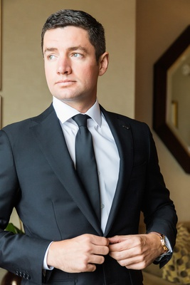 groom in suitsupply classic black suit with white shirt and black tie