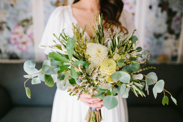 bride in boho dress holding loose bouquet seasonal greenery with pale yellow ranunculus and dahlia
