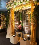 Gold oversized mirror with flowers on top displaying calligraphy names of guests and their tables