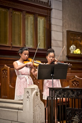 bride's daughters junior bridesmaids dress with lace overlay, play violin at ceremony