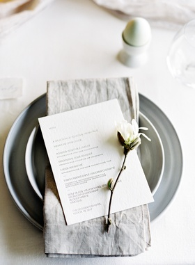 grey charger plate, grey napkin, dinner menu with sprig of magnolia, bridal shower
