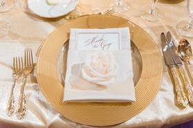 Wedding guest place setting with gold charger gilt flatware silverware and single white rose on menu