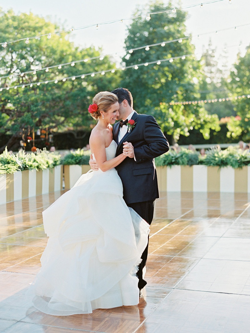Bride in Vera Wang wedding dress with red flower in hair dances with groom on large dance floor