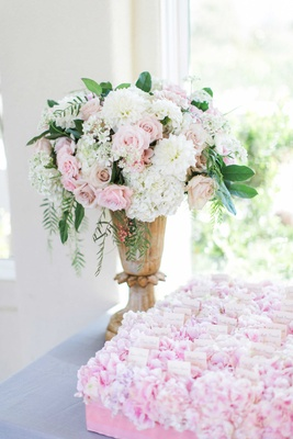 Urn filled with white hydrangea, pink rose, and green leaves at escort card table with pink flowers