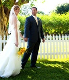 Bride and groom in front of white picket fence