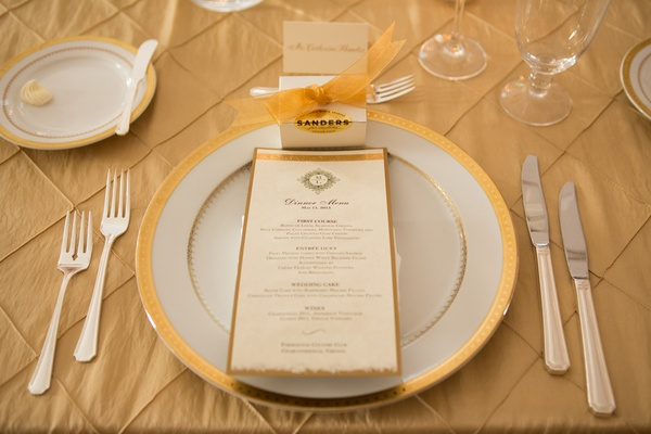 White and gold charger plate with menu card and wedding favor