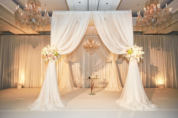 Dreamy chuppah decorated with white tulles and some pretty flower arrangements