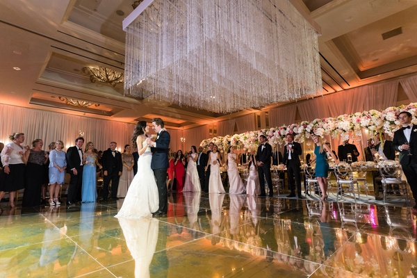 Bride in monique lhuillier wedding dress on dance floor gold with crystal ceiling installation over