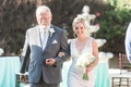 Bride in a sleeveless Claire Pettibone dress is escorted by father of bride in grey suit