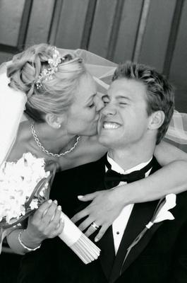 Black and white photo of bride kissing groom's cheek