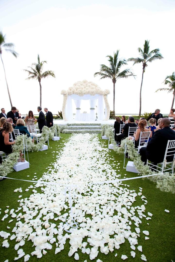 White flower petals on grass aisle lead to white flower chuppah