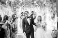 Black and white photo of black tie wedding bride and groom holding hands leaving ceremony space