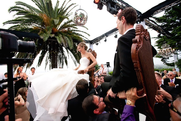 Guests lift bride and groom in chairs for Jewish tradition