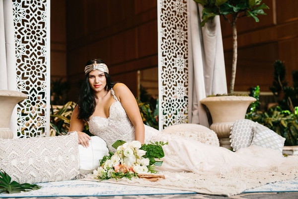 wedding with laser cut arch bride with headband and low cut wedding dress on layered rugs pillows