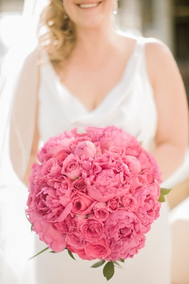 Blonde bride holding round arrangement of peonies and roses