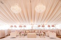 wedding reception tent drapery chandelier lounge area sofa ottoman table gold pink flowers