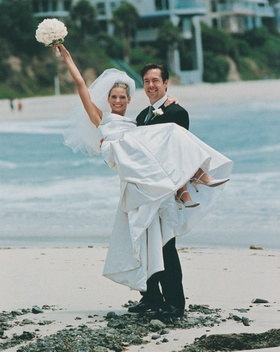 Groom holds bride on Laguna Beach sand