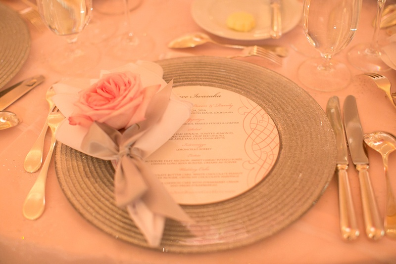Pink rose with silver ribbon on silver charger at wedding