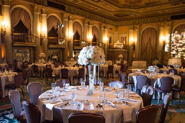 Wedding reception table with tall centerpiece topped with white flowers and suspended crystals