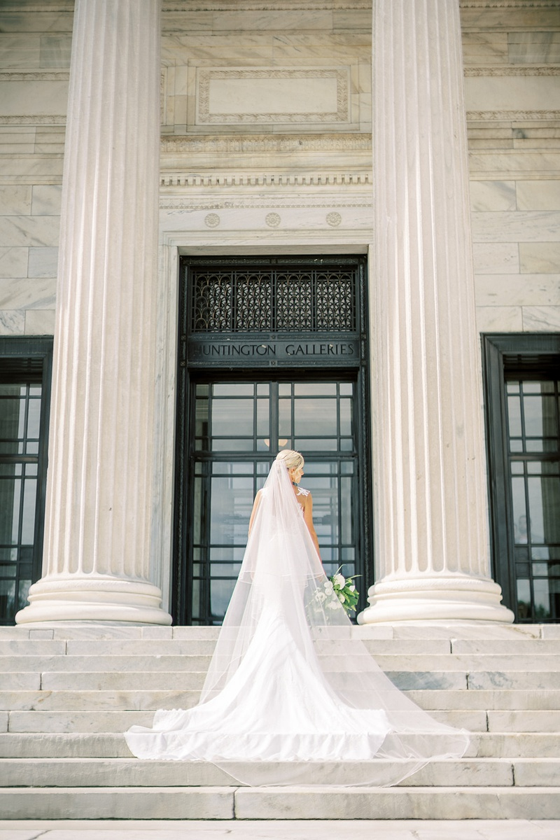 bride in form fitting pronovias wedding dress wearing cathedral veil on blonde hair updo